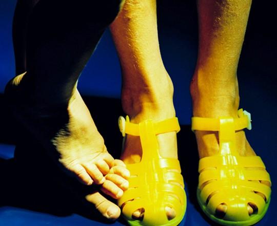 Kinderfüße, gelbe Plastiksandalen